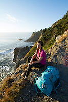 Young woman backpacking the Oregon Coast Trail. Oswald West State Park, OR.