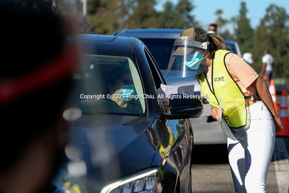 A worker gives directions as motorists wait in lines to get the coronavirus (COVID-19) vaccine in a parking lot at Dodger Stadium, Friday, Jan. 15, 2021, in Los Angeles. Dodger Stadium reopened Friday as a mass COVID-19 vaccination site, which Mayor Eric Garcetti says will have the capacity to vaccinate 12,000 people a day once it is fully operational.