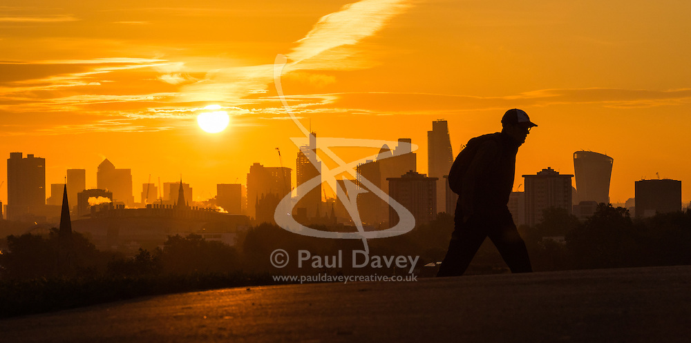 Primrose Hill, London, October 28th 2016. An early morning walker reaches the summit of Primrose Hill as the sun rises over London's skyline.