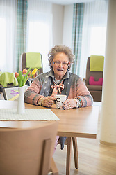 Senior woman with coffee at rest home