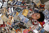 Tacoma librarian Lara Weigand is buried by some of the 519 music CD's considered surplus. (AP Photo/John Froschauer)