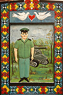 Tombstone of an army  tank driver,   The  Merry Cemetery ( Cimitirul Vesel ),  Săpânţa, Maramares, Northern Transylvania, Romania.  The naive folk art style of the tombstones created by woodcarver  Stan Ioan Pătraş (1909 - 1977) who created in his lifetime over 700 colourfully painted wooden tombstones with small relief portrait carvings of the deceased or with scenes depicting them at work or play or surprisingly showing the violent accident that killed them. Each tombstone has an inscription about the person, sometimes a light hearted  limerick in Romanian. .<br /> <br /> Visit our ROMANIA HISTORIC PLACXES PHOTO COLLECTIONS for more photos to download or buy as wall art prints https://funkystock.photoshelter.com/gallery-collection/Pictures-Images-of-Romania-Photos-of-Romanian-Historic-Landmark-Sites/C00001TITiQwAdS8