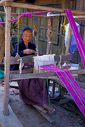 Asia, Thailand, Northern Thailand, Mae Na Chan Village, Woman at hand loom weaving delicate fabric by traditional method