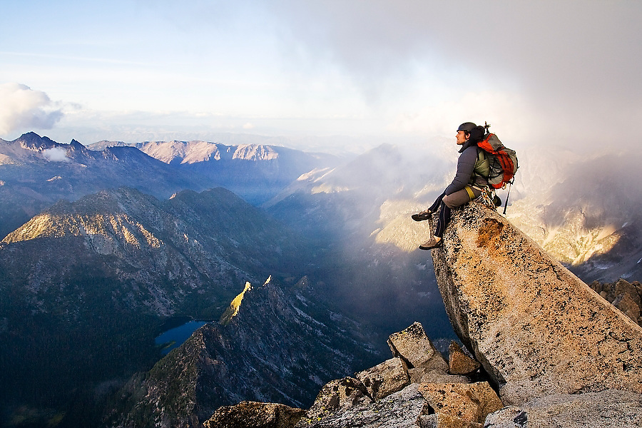 Climber Kris Haskins sits on the summit of Mount Stuart after a successful ascent by the West Ridge, Alpine Lakes Wilderness, Washington. Mount Stuart is the second highest non-volcanic peak in the state.