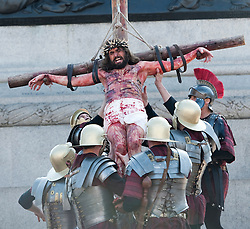 © London News Pictures. 06/04/2012. London, UK.  An actor playing jesus is placed on the cross by roman soldiers during a performance of The Passion of Jesus  in front of thousands of people in Trafalgar Square in central London, England on  April 6, 2012  to mark Good Friday. The actors come from the Wintershall Estate in Surrey. Photo credit :  Ben Cawthra/LNP