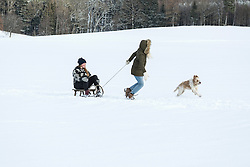 Two girls and a dog with slide in snowy landscape in winter, Bavaria, Germany