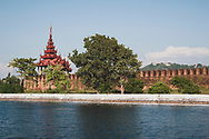 Mandalay, Myanmar - November 8, 2011: Walls and moat outside the Mandalay Palace. In the distance in Mandalay Hill