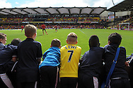 Young Watford fans watch the players warming up from the touchline. Barclays Premier League, Watford v Southampton at Vicarage Road in London on Sunday 23rd August 2015.<br /> pic by John Patrick Fletcher, Andrew Orchard sports photography.