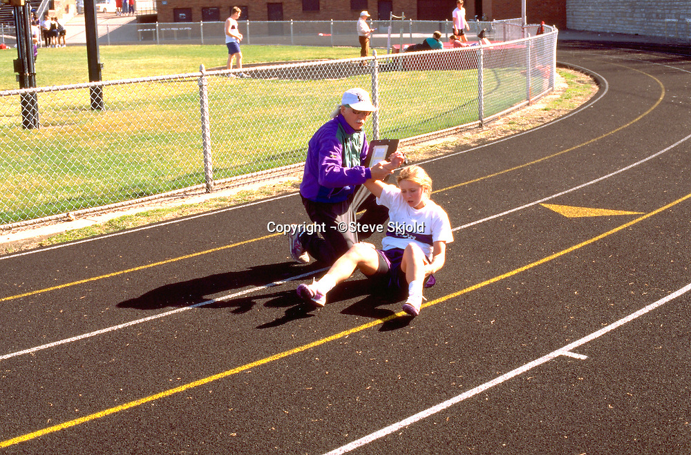 Coach and runner ages 51 and 16 helping her up from a fall.  St Paul Minnesota USA