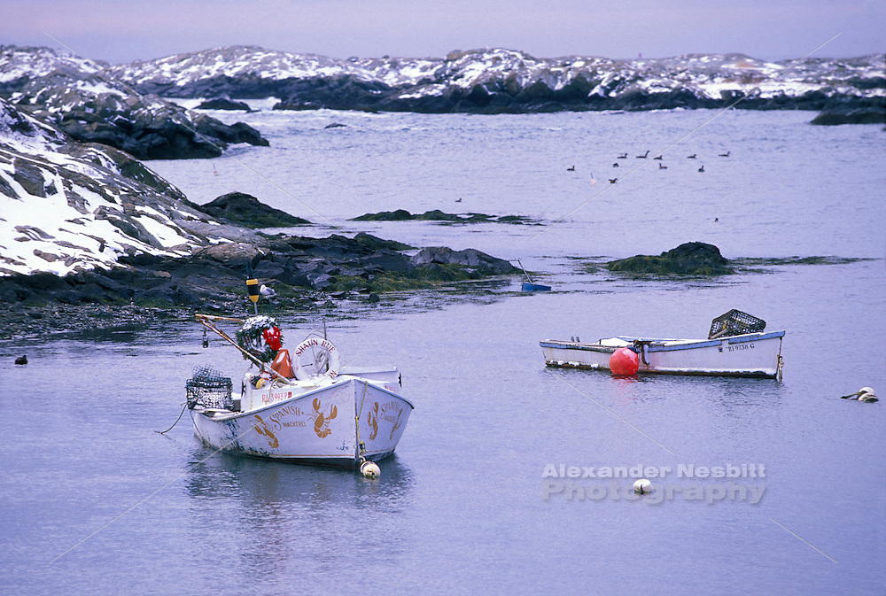 "Usa, Newport, RI - A dusting of snow covers the area while rustic lobstering skiffs hang at their moorings in the inlet near Green Bridge on the Ocean Drive.  A seagull and Christmas wreath adorn the skiff named ""Spanish Mackerel"""