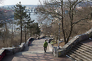 A Prague citizen descends Stalinist-era steps in Letna Park (Letenske Sady), on 18th March, 2018, in Prague, the Czech Republic. Up until it was destroyed by Soviet leader Nikita Kruschev, the largest statue to Stalin in the entire Eastern Bloc was located here. It is now a favourite place skateboard park, dog walkers and families. Like Rome, Prague is built on seven hills.