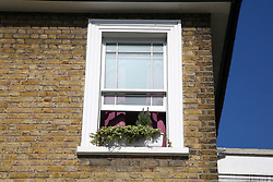 © Licensed to London News Pictures. 28/05/2020. London, UK. An open window at a residential property on Southgate Road, Islington, in north London. Police were called just after 8pm on Wednesday, 27 May following a domestic incident and found two pensioners - one man and a woman in their 70s suffering from stab wounds. Victims were taken to a hospital and are fighting for their lives. Photo credit: Dinendra Haria/LNP