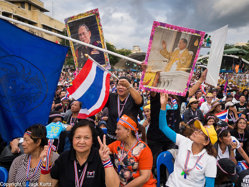 "15 NOVEMBER 2013 - BANGKOK, THAILAND:  Thai royalists wave photos of Bhumibol Adulyadej, the King of Thailand, during a anti-government protest in Bangkok. Thai royalists accuse the government of Prime Minister Yingluck Shinawatra of not being supportive enough of the monarchy. Tens of thousands of Thais packed the area around Democracy Monument in the old part of Bangkok Friday night to protest against efforts by the ruling Pheu Thai party to pass an amnesty bill that could lead to the return of former Prime Minister Thaksin Shinawatra. Protest leader and former Deputy Prime Minister Suthep Thaugsuban announced an all-out drive to eradicate the ""Thaksin regime."" The protest Friday was the biggest since the amnesty bill issue percolated back into the public consciousness. The anti-government protesters have vowed to continue their protests even though the Thai Senate voted down the bill, thus killing it for at least six months.     PHOTO BY JACK KURTZ"