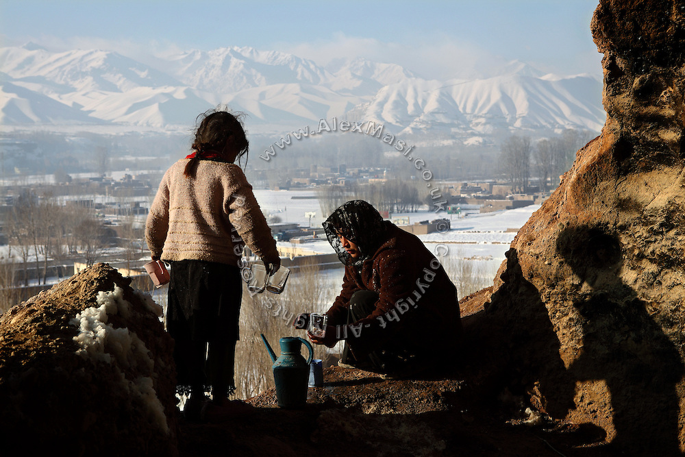 Kobra, 17, (Right) is washing some cups to prepare tea while being helped by Hamidah, 6, (Left) near to the entrance of the cave their families live in since seven years, during a cold winter morning in Bamyan, central Afghanistan, an area mostly populated by Hazaras. A historically persecuted minority (15%) due to more lenient Islamic faith and characteristic 'Eastern' lineaments, Hazaras constitute the 70% of Bamyan's population.