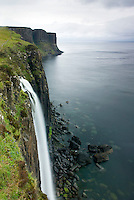Waterfall flowing over the cliffs of the coast of Isle of Skye Scotland, Kilt Rock is in the distance.
