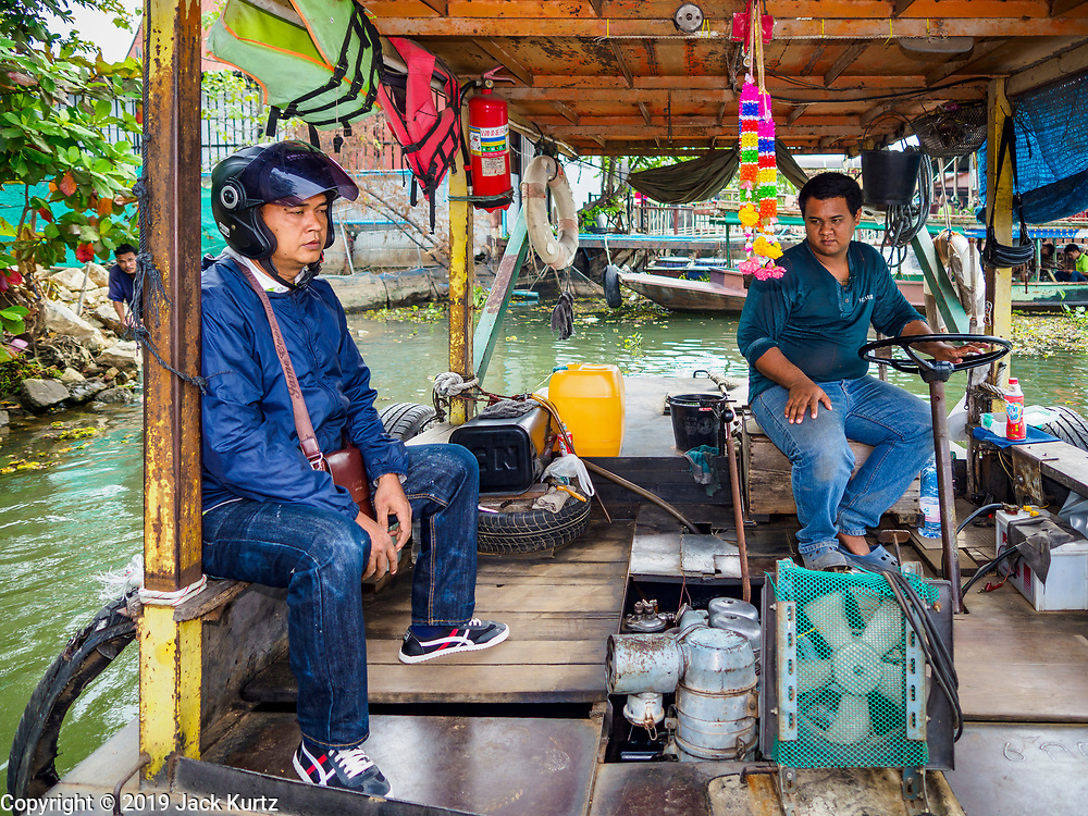 "09 JANUARY 2019 - KANCHANABURI, THAILAND: A passenger sits with BOM, the operator of a small ferry on the River Kwai near Kanchanaburi. The ferry goes across the River Kwai downriver from downtown Kanchanaburi, the site of the famous ""Bridge on the River Kwai."" Small ferries like this, once common on Thai river crossings, are disappearing because Thailand has dramatically improved its infrastructure since this ferry started operating about 50 years ago. The ferry operator said his grandfather started the ferry, with a small raft he would pole across the river, in the late 1960s. Now his family has a metal boat with an inboard engine. There are large vehicle bridges across the river about 5 miles north and south of this ferry crossing, but for people in rural communities on the west side of the river the ferry is still the most convenient way to cross the river.      PHOTO BY JACK KURTZ"