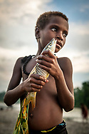 A young girl named Stesie holds a freshly caught fish beside the Clay River in the village of Likan, located in East Sepik Province in Papua New Guinea.