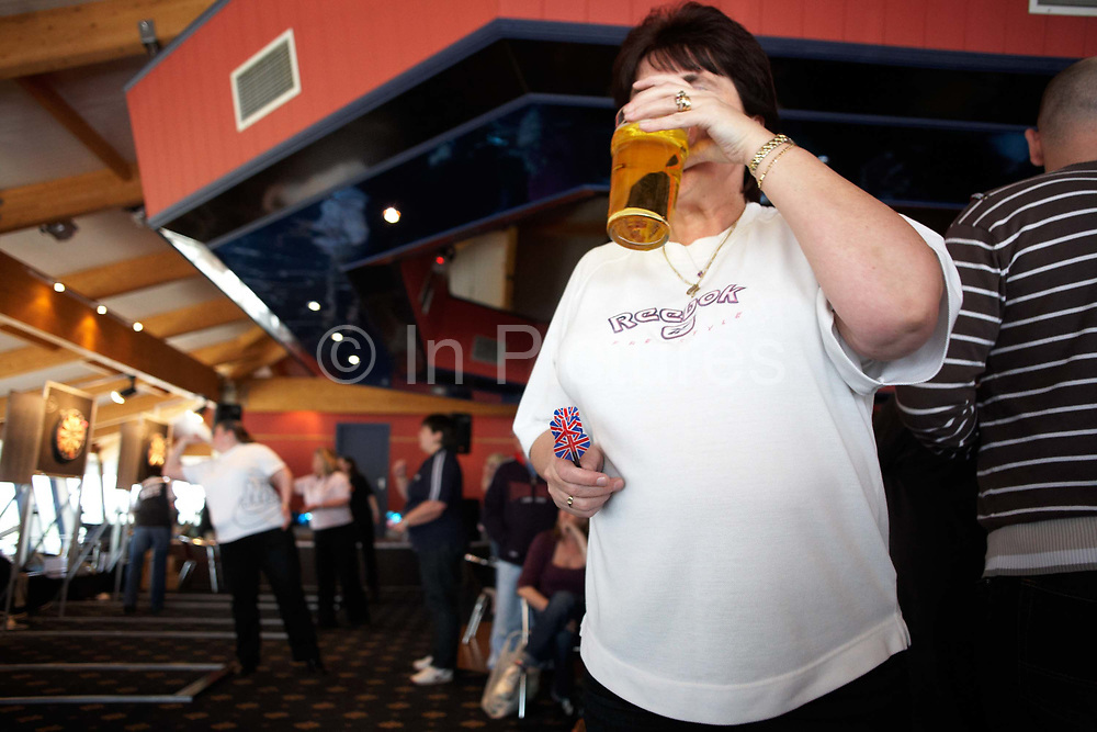 A large, manly woman sips a pint of lager during a darts tournament where she competes in an England Open tournament at the Bunn Leisure Holiday Park in Selsey, near Chichester on the south coast of England. Holding three darts with a Union Jack flags on the 'flights', her glass covers her face but we see her rings and bracelet and her ample belly after a life of beer and cigarettes in pubs like this. A great deal of alcohol (mostly lager, but also Coke) is consumed during darts tournaments although smoking in public places has now been banned in the UK, including pubs and bars. This audience seemed to consist largely of very large lesbian women from working families which seems to suggest that the pub (and alcohol) is still the place where women are attracted to the game of darts.
