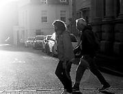 A couple stroll Cheltenham High Street, UK, wearing masks in preparation of national lockdown on 3rd of November 2020.