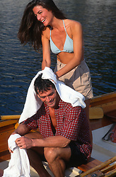 Woman drying a man off in a rowboat on a lake