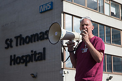 Staff nurse David Carr addresses NHS staff preparing to march from St Thomas' Hospital to Downing Street to protest against the NHS Pay Review Body's recommendation of a 3% pay rise for NHS staff in England on 30th July 2021 in London, United Kingdom. The protest march was supported by Unite the union, which has called on incoming NHS England Chief Executive Amanda Pritchard to ensure that a NHS pay rise comes from new Treasury funds rather than existing NHS budgets and which is shortly expected to put a consultative ballot for industrial action to its members.