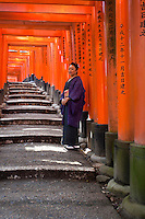 Woman in Kimono at Fushimi Inari Shrine, a Shinto shrine dedicated to Inari, the god of rice, sake, and prosperity. .One of Kyoto's oldest and most revered Shinto shrines, Fushimi Inari serves as the headquarters for all the 40,000 shrines dedicated to Inari across Japan..Fushimi Inari is noted for its remarkable sight of some 10,000 small torii shrine gates that arch over a long path up the hill behind the shrine.