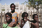 Children in front of the mud-walled mosque (Muslim) in the W. African town of San, Mali. Material World Project.