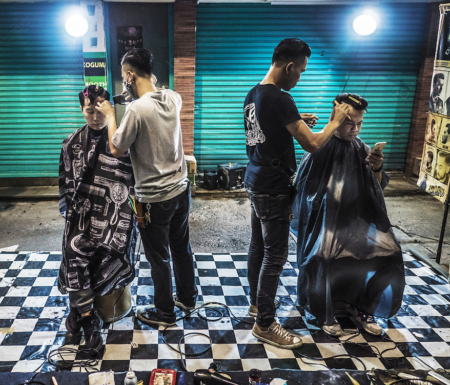 Two barbers working and cutting hair in rockabilly style at a street in Patpong area red light district Bangkok Thailand