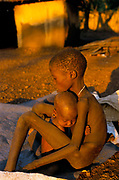 A baby clings to his malnourished brother at an aid agency feeding centre. Ajiep, Bahr el Ghazal, Sudan. The famine in Sudan in 1998 was a humanitarian disaster caused mainly by human rights abuses, as well as drought and the failure of the international community to react to the famine risk with adequate speed. The worst affected area was Bahr El Ghazal in southwestern Sudan. In this region over 70,000 people died during the famine.