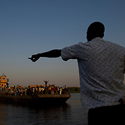 A man points instructions to the crew of a barge carrying hundreds of South Sudanese arriving in Juba ahead of the referendum for independence of South Sudan.