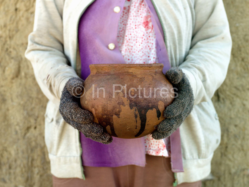 A Hindu Cham woman holds a newly-fired ceramic pot made using a traditional method in Duc Binh village in Binh Thuan province, Central Vietnam. Cham potters do not use a wheel to make pots, instead clay is pressed into shape using the hands. Layers of clay are added to the original piece and the potter moves around the object, pressing the clay into the desired shape. They are then put directly in the sun and completely bone dried, making them ready to be fired. Firing is done in an open pit with temperatures going up to 800 degree Celcius. The pots are arranged together and covered with layers of rice straw, which is set on fire.