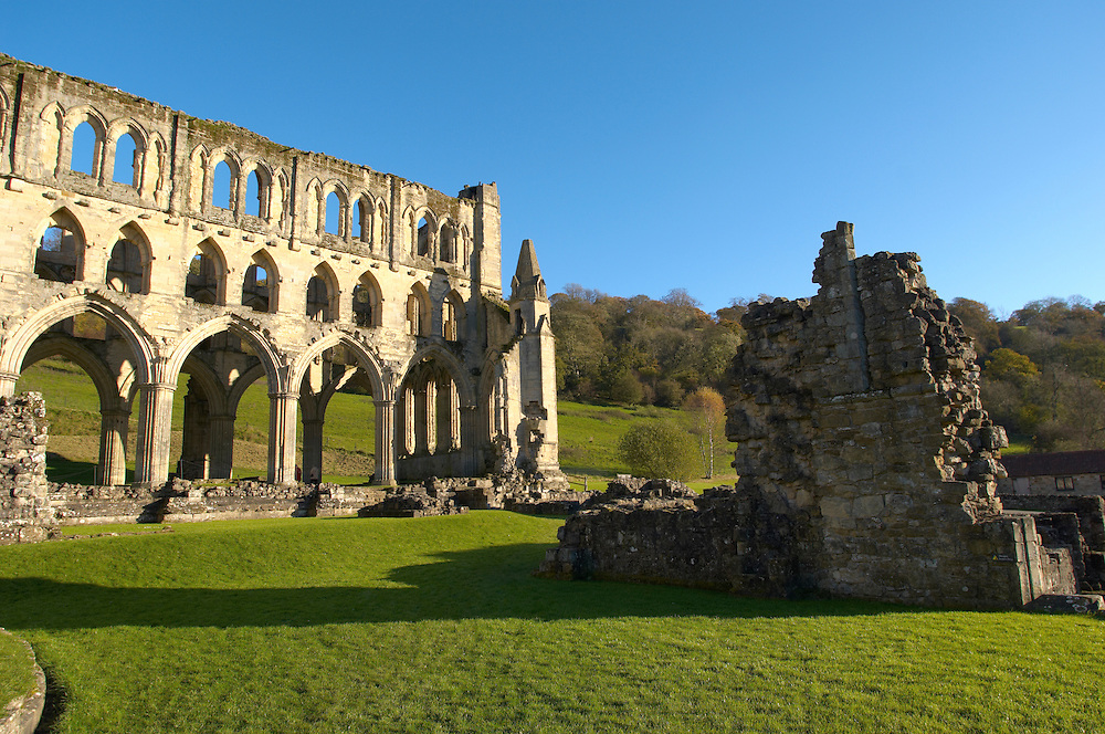 Rievaulx Abbey main church, side view.North Yorkshire, England . Rievaulx Abbey was a Cistercian abbey in Rievaulx, situated near Helmsley in the North York Moors National Park, North Yorkshire, England. Rievaulx Abbey was one of the great abbeys in England until it was seized under Henry VIII of England in 1538 during the dissolution of the monasteries. Founded in 1132 by twelve monks from Clairvaux Abbey. Rievaulx Abbey remote location was well suited to the order's ideal of a strict life of prayer and self-sufficiency with little contact with the outside world. <br /> <br /> Visit our MEDIEVAL PHOTO COLLECTIONS for more   photos  to download or buy as prints https://funkystock.photoshelter.com/gallery-collection/Medieval-Middle-Ages-Historic-Places-Arcaeological-Sites-Pictures-Images-of/C0000B5ZA54_WD0s