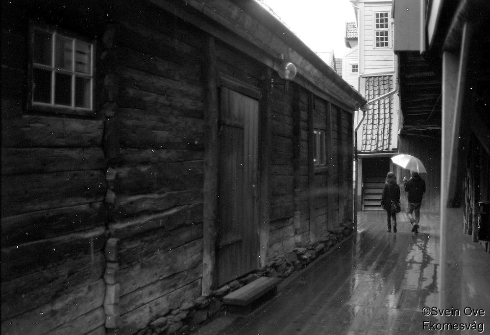 Et par spaserer under paraplyen langs Bryggen i Bergen.<br /> Foto: Svein Ove Ekornesvåg