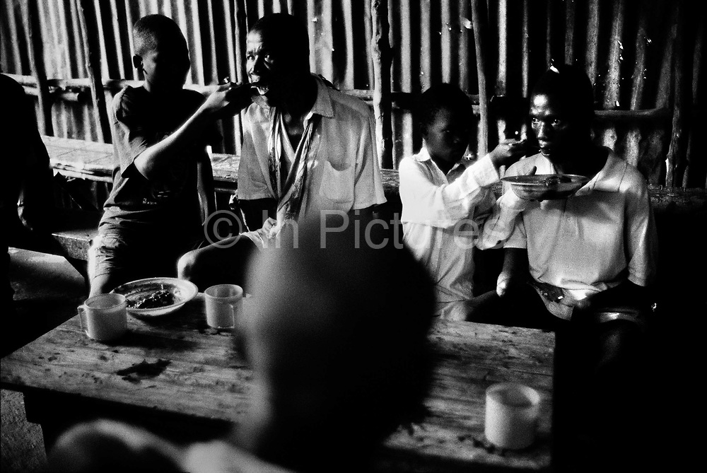 Hassan Fufona and another victim of the amputations are fed by boys af a cafe after begging. Freetown, Sierra Leone 1999