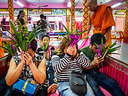 "29 MARCH 2017 - BANG KRUAI, NONTHABURI, THAILAND: A family sits up in a coffin representing their rebirth during a ""Resurrection Ceremony"" at Wat Ta Kien (also spelled Wat Tahkian), a Buddhist temple in the suburbs of Bangkok. People go to the temple to participate in a ""Resurrection Ceremony."" Groups of people meet and pray with the temple's Buddhist monks. Then they lie in coffins, the monks pull a pink sheet over them, symbolizing their ritualistic death. The sheet is then pulled back, and people sit up in the coffin, symbolizing their ritualist rebirth. The ceremony is supposed to expunge bad karma and bad luck from a person's life and also get people used to the idea of the inevitability of death. Most times, one person lays in one coffin, but there is family sized coffin that can accommodate up to six people. The temple has been doing the resurrection ceremonies for about nine years.          PHOTO BY JACK KURTZ"
