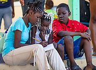 Chelsea Michel, 12, helps Alicia St. Remy, 6, with her vocabulary words as JC Emmanuel Michel, 9, looks on, on Saturday, Sept. 7, 2019. The children have been living at a storm shelter in Marsh Harbour, Abaco, since Hurricane Dorian ravaged the Bahamas.