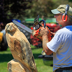 Intercourse, PA - June 18, 2016: A wood carver uses a chain saw to sculpt an eagle from a log in the Community Park at the Intercourse Heritage Days event.