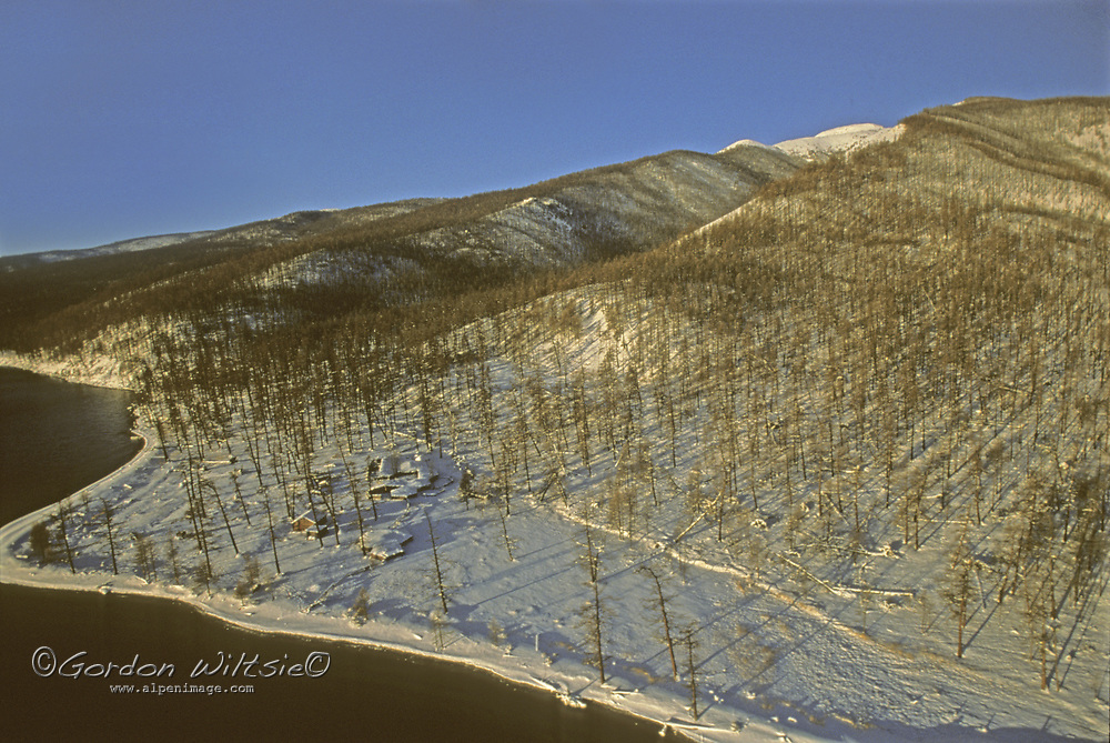 MONGOLIA. West shore of Lake Hovsgol, with a nomadic family's winter camp below the slopes of Horidol Saridag Mountains.