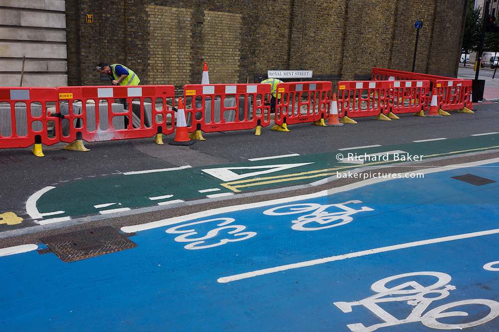 Two contractors lay fresh paving stones from behind protective street health & safety barriers.
