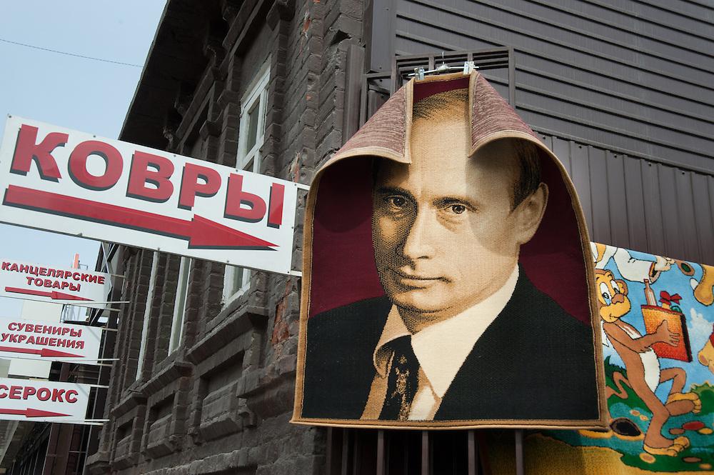 A carpet portrait of Russian President Vladimir Putin hangs beside a carpet with a cartoon illustration in a market in Irkutsk Siberia.