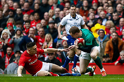 Keith Earls of Ireland under pressure from Josh Adams of Wales<br /> <br /> Photographer Simon King/Replay Images<br /> <br /> Six Nations Round 5 - Wales v Ireland - Saturday 16th March 2019 - Principality Stadium - Cardiff<br /> <br /> World Copyright © Replay Images . All rights reserved. info@replayimages.co.uk - http://replayimages.co.uk