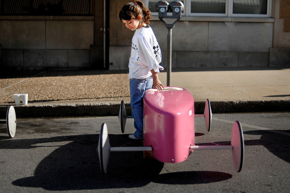 """Haley McKernan, 8, lays a hand on her soap box racing car """"Haley's Comet"""" before the start of her first competition. Her father and grandfather helped her build the car including the recent paint job with her favorite color, pink."""