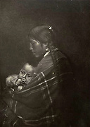 North American Indian woman with plaited hair,  holding her infant.
