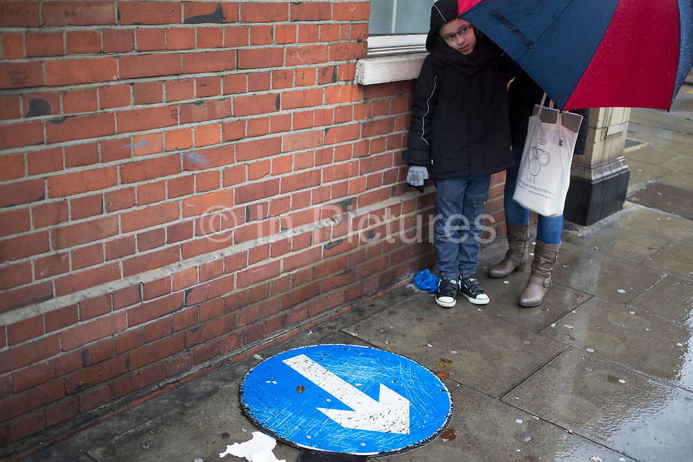 Mother and son shelter from the rain beside a road sign on a wet rainy day in Whitechapel, East End of London, UK.