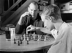 Father playing chess against young son,