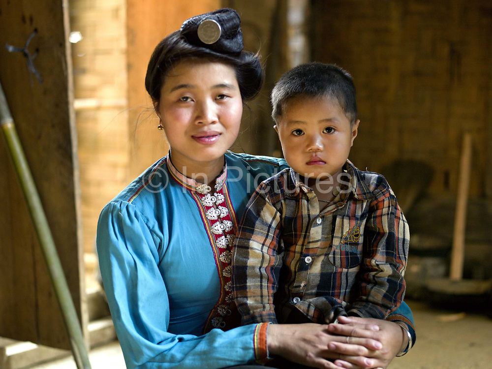 A portrait of Laep, a Tai Dam ethnic minority woman and her young son in her home in Ban Nam Bone village, Phongsaly province, Lao PDR. Tai Dam married women are easily recognised by their topknots, affixed with a silver hairpin and their tight-fighting blouses which can be one of many different colours. One of the most ethnically diverse countries in Southeast Asia, Laos has 49 officially recognised ethnic groups although there are many more self-identified and sub groups. These groups are distinguished by their own customs, beliefs and rituals. Details down to the embroidery on a shirt, the colour of the trim and the type of skirt all help signify the wearer's ethnic and clan affiliations.