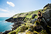 Woman out for a run on the north coast cliff paths, stopping to sit on a rock and take in the views out to sea in Jersey, Channel Islands