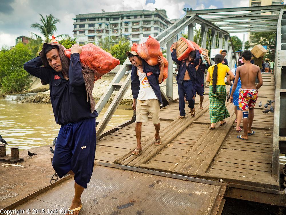 03 NOVEMBER 2015 - YANGON, MYANMAR: Stevedores carry cargo down to a boat on the Yangon docks.    PHOTO BY JACK KURTZ