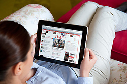 Woman using iPad tablet computer to read Time magazine online