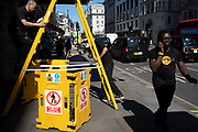 Yellow street scene with workmen and their ladder doing maintenance work in a cordoned off area on a building along Piccadilly in London, United Kingdom.